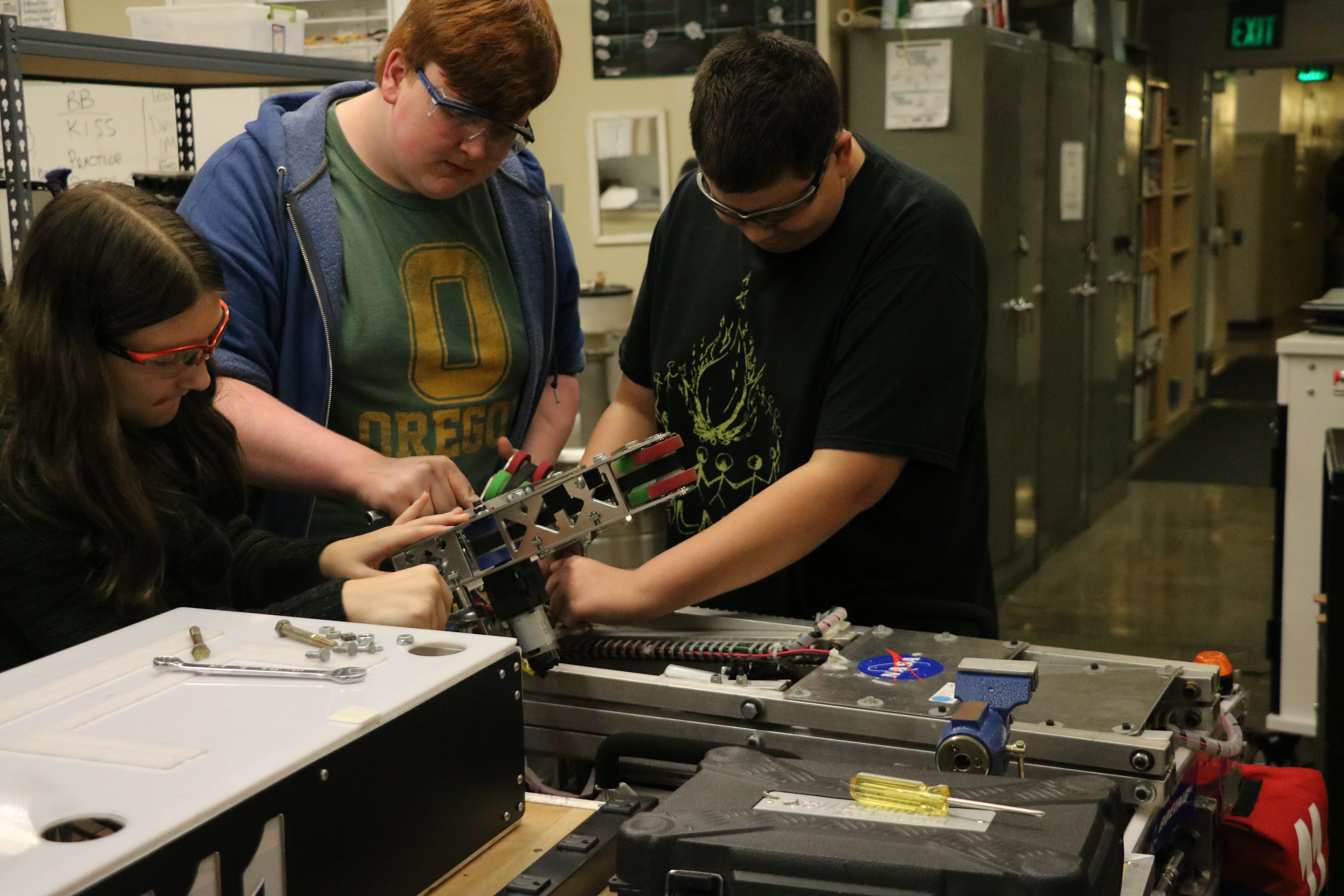 Several team mates working on disassembling various parts of a robot.